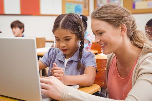 Cute pupil using computer with teacher