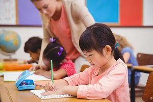 Cute pupils writing at desk in classroom