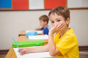 Thoughtful pupil sitting at his desk