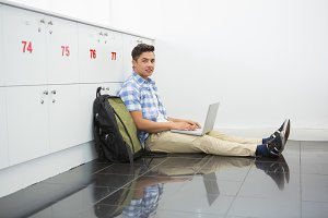 Smiling college student sitting on the floor with laptop