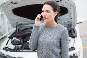 Annoyed woman on the phone beside her broken down car