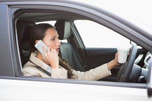 Woman drinking coffee on phone while driving