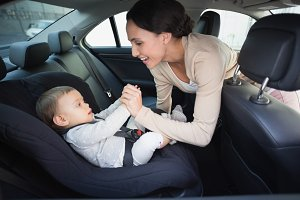 Mother securing her baby in the car seat