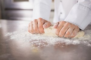 Close up of baker preparing dough