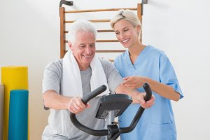 Senior man doing exercise bike with therapist
