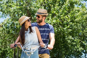 Hipster couple on a bike ride in the park