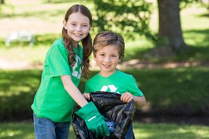 Happy siblings collecting rubbish