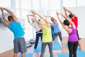 People doing stretching exercise in yoga class