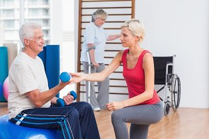 Trainer assisting senior man in exercising with dumbbells