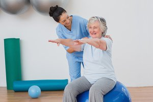 Instructor assisting senior woman in exercising