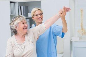 Nurse helping senior patient in exercising