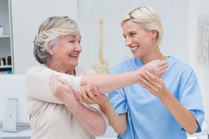 Happy nurse assisting patient in raising arm