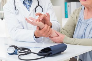 Doctor examining patients hand at table