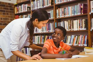 Teacher assisting boy with homework in library