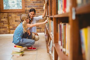 Teacher and little girl selecting book in library