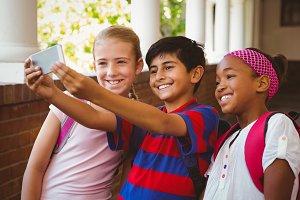 Happy kids taking selfie in school corridor
