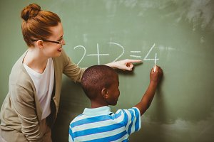 Teacher assisting boy to write on blackboard in classroom