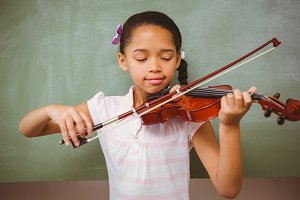 Portrait of cute little girl playing violin