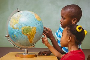 Kids pointing at globe in classroom