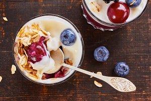 Two yogurt desserts with berries and muesli.
