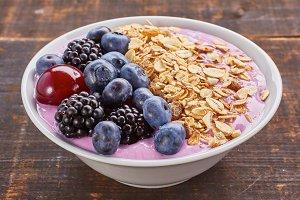 Dish of yogurt smoothie, fresh berries and muesli