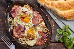 Pan of fried eggs with onion, ham and chard