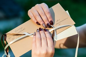 Women's hands holding mail envelope