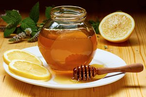 Jar of honey over white plate with dripper, lemon slices and flowering mint