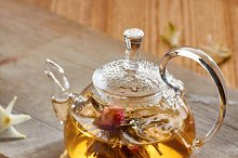 Glass teapot and two cups with green tea