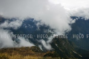 Clouds rising up the mountains, colorful autumn landscape