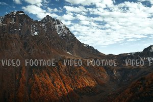 timelapse of Golden mountain hills, snow tops and red forest. cloud shadows show relief