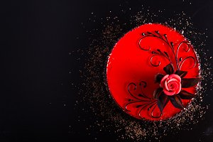 Red Cake with rose on black background. Top view. Valentine's Day. Free space for your text.