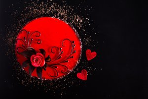 Red Cake with rose, two hearts on black background. Top view. Valentine's Day. Free space for your text.