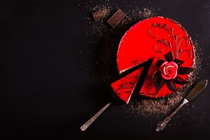 Red cake with rose, chocolate flower, on dark background. Free space for your text. Selective focus