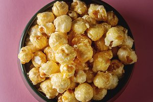 Sweet popcorn in a bowl. bright background. Watch a movie.