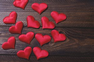 Many red hearts on brown wooden table.