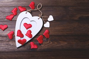 White wooden heart with many red hearts on brown wooden table.