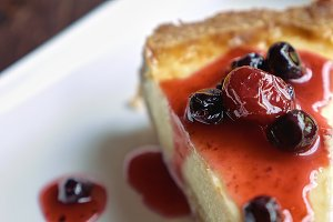 Cheesecake piece topped with fruit sauce