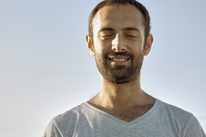 Cheerful man smiles with eyes closed