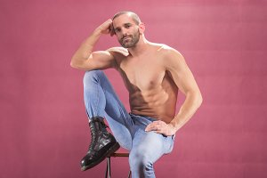 man sitting muscular pink background