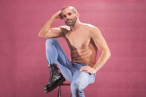 man sitting muscular pink background