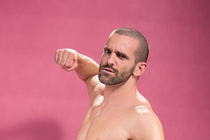 man punching fist pink background