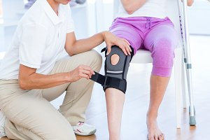 Doctor examining her patients knee