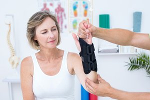 Doctor examining his patients wrist