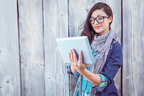 Happy hipster holding a tablet pc