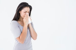 Sick brunette blowing her nose