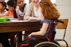 Teacher helping a disabled pupil