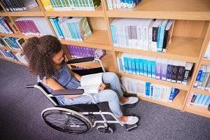 Smiling disabled student in library reading book