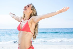 Smiling blonde in bikini arms outstretched