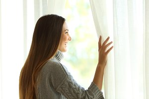 happy woman opening curtains